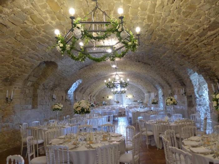 La Sala d'Armi apparecchiata per un matrimonio. Festoni di rose addobbano i tre lampadari