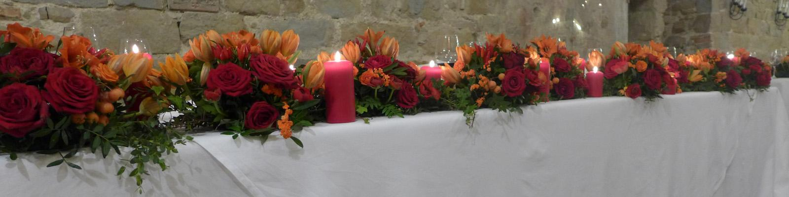 Runner of flowers in the shades of red and orange for the high table